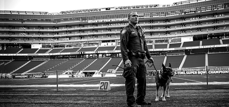 officer with K-9 Officer in stadium