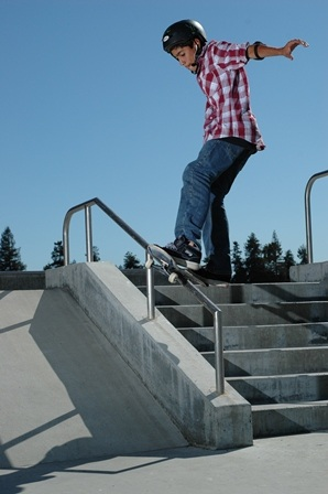 a skateboarder going down a  railing very, very, carefully