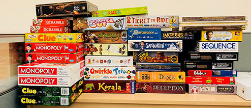 many boardgames stacked on a shelf